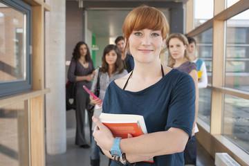 Deutschland, Leipzig, Frau lächelnd, Studenten stehen im Hintergrund