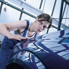 Deutschland, Augsburg, Arbeiter Blick auf glänzenden Auto nach Auftragen von Wachs