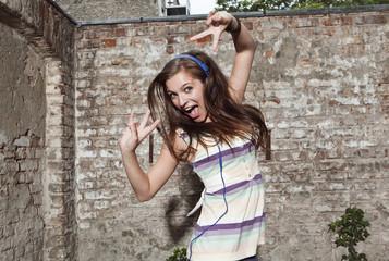 Deutschland, Berlin, Junge Frau trägt Kopfhörer, tanzen, lächeln