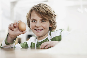 Deutschland, Köln, Junge hält Ei, Lächeln