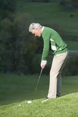 Italien, Kastelruth, erwachsener Mann spielt Golf auf dem Golfplatz