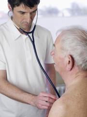 Deutschland, Hamburg, Doktor, der Patienten mit Stethoskop in der Klinik untersucht