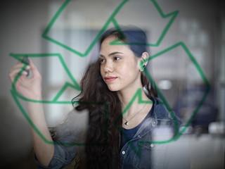 Deutschland, Köln, Junge Frau Zeichnung Recycling-Symbol auf Glas