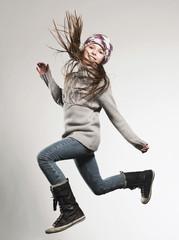 Mädchen trägt Wollmütze springend, Lächeln