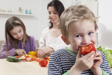 Deutschland, Bayern, München, Mutter und Tochter bereitet Salat, Sohn isst