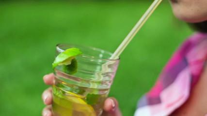 Close up of woman mouth drinking fresh lemonade