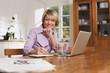Deutschland, Kratzeburg, erwachsene Frau mit Notizbuch und Laptop