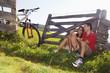 Paar sitzt auf der Wiese, stützte sich auf Holzgeländer
