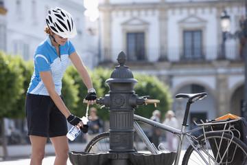 Spanien, Andalusien, Frau füllt Wasser in die Flasche von Trinkbrunnen