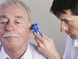 Deutschland, Hamburg, Arzt untersucht Patienten mit Otoskop