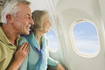 Deutschland, München, Bayern, älteres Paar, Senioren Blick durch das Fenster in der Economy-Klasse Verkehrsflugzeug