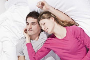 Junges Paar liegt auf dem Bett, die Augen geschlossen