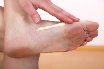 A woman putting cream on her foot
