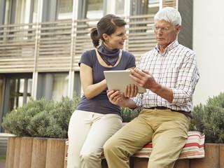 Deutschland, Köln, erwachsener Mann und junge Frau, Tablet-PC außerhalb Pflegeheim
