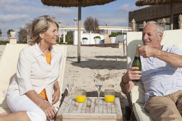 Spanien, Mallorca, älteres Paar, Senioren mit Getränk am Strand