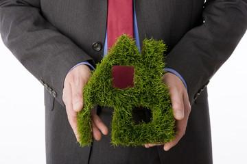 Person, die Haus-Symbol aus Gras macht