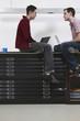 Männer sitzen von Angesicht zu Angesicht mit Laptop