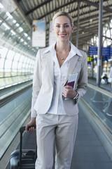 Deutschland, Leipzig-Halle, Flughafen, Junge Frau mit Koffer auf Transportband, Rollband, Fahrsteig