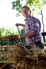 Deutschland, Sachsen, erwachsener Mann arbeitet auf dem Bauernhof