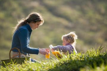 Mutter mit Tochter sitzen auf der Wiese, Mutter gießt Saft ein