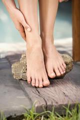 Frau berührt ihr Bein