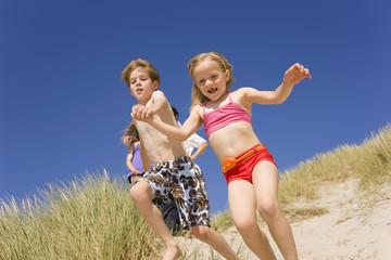 Deutschland, Ostsee, Junge und Mädchen springen am Strand von Düne