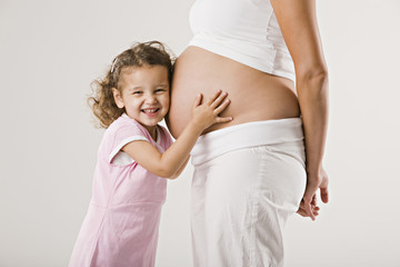 Mädchen umarmt Bauch der schwangeren Mutter
