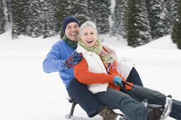 Italien, Südtirol, Seiseralm, älteres Paar, Senioren Rodeln den Berg hinunter, lachen