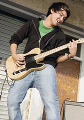 Deutschland, Augsburg, Junger Mann spielt eine E-Gitarre