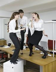 Deutschland, Köln, Junge Frauen, die Spaß mit Sekthaben, im Büro