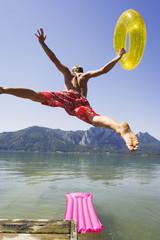 Österreich, Salzkammergut, Mondsee, Junger Mann springt ins Wasser