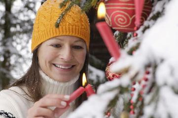 Junge Frau schmückt Weihnachtsbaum im Schnee