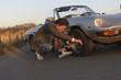 Deutschland, Hamburg, Mann wechelt Reifen eines alten Autos