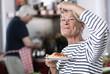 Deutschland, Wakendorf, erwachsene Frau isst Nudeln, Mann kocht im Hintergrund
