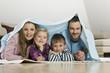Familie bedeckt mit Decke