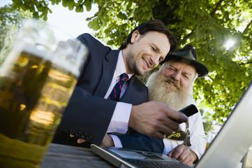 Deutschland, Bayern, Oberbayern, Alter Bayer und junger Geschäftsmann mit Laptop in Biergarten