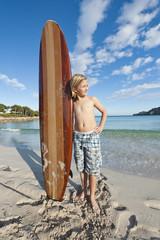 Spanien, Mallorca, Junge mit Surfbrett am Strand
