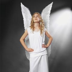 Mädchen als Engel vor schwarzem Hintergrund