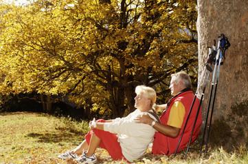 älteres Paar, Senioren sitzt auf der Wiese, Mann lehnt am Baum, Seitenansicht