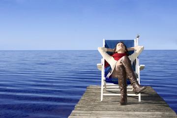 Junge Frau sitzt im Liegestuhl am Steg, die Augen geschlossen