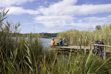 Italien, Toskana, Lago dell'Accesa, Mountainbiker, die eine Pause am Seeufer