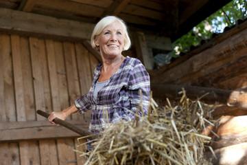 Deutschland, Sachsen, erwachsene Frau, die auf dem Bauernhof arbeitet