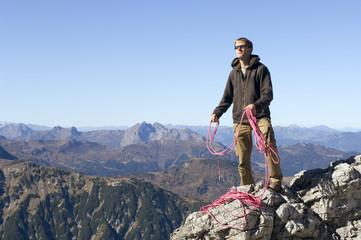 Österreich, Salzburger Land, Junger Mann mit einem Seil vor Bergwelt
