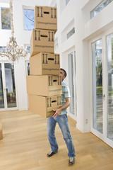 Deutschland, Bayern, Gröbenzell, erwachsener Mann mit Stapel von Kartons