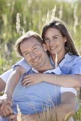 Deutschland, Bayern, Mann und Frau umarmen in Wiese