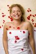Deutschland, junge Frau auf einem Massagetisch mit Blütenblättern auf der Brust