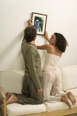 Junges Paar hängt Bild auf
