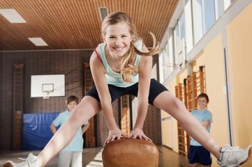 Deutschland, Emmering, Mädchen springend mit Jungen, die im Hintergrund
