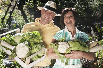 Österreich, Salzburg, Flachau, Paar hält Gemüse im Garten, Lächeln