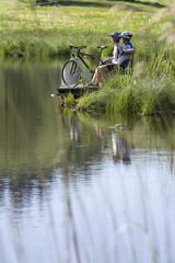 Deutschland, Bayern, Paar mit Mountainbikes entspannt am Seeufer